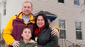Family standing in front of a house