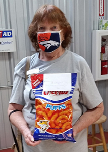 Food Bank volunteer Evelyn holding a bag of Cheetos.