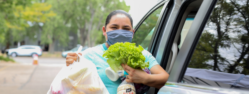Food Bank client loads food into her car during COVID-19.