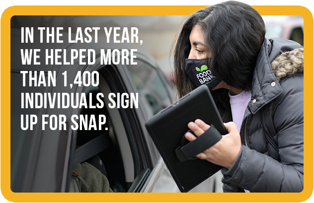 Image of a Food Bank employee assisting a client in signing up for SNAP benefits.