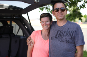 A couple - Holly and Craig - pose by their vehicle.