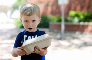 Little boy holds food tray at the Lunch Lab.