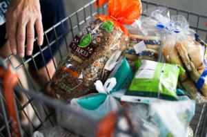 Image of a full shopping cart of food at the Food Bank.