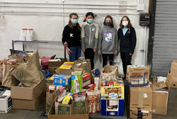 Food Bank fundraiser - young girls donating food.